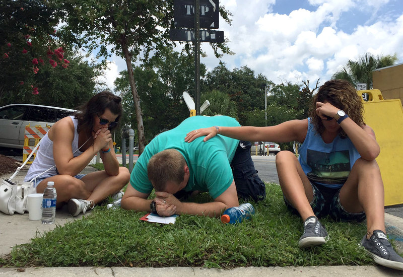 People pray on Orange Ave. in Orlando, near the Pulse night club. Hansi Lo Wang/NPR
